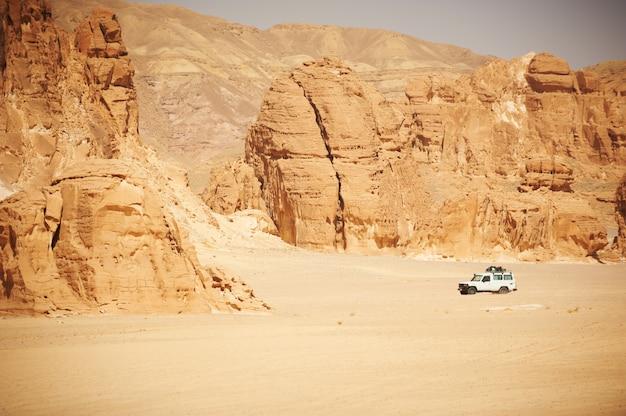 サファリのための岩とジープのあるシナイ砂漠の風景。