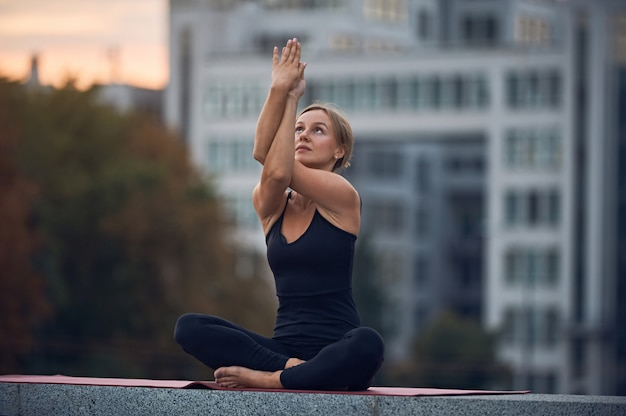 Красивая молодая женщина практикует йогу асаны гарудасана - орлиная поза на открытом воздухе