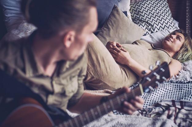 ギターを弾く男と妊娠中の妻がロフトルームのベッドに横たわっています。