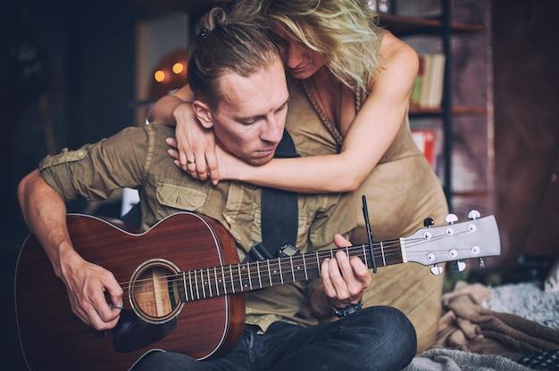 ギターを弾く男と妊娠中の妻がロフトルームのベッドに座っています。