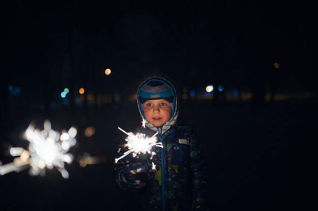 Мальчик держит бенгальский огонь в руках во время празднования нового года на улице в ночное время.