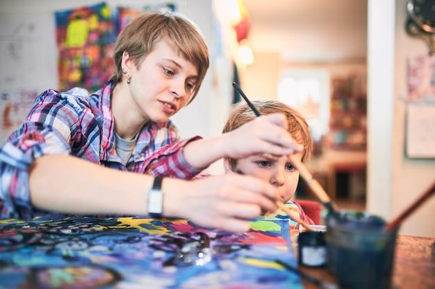 かわいい幸せな男の子とアーティストのクラスで描く先生。