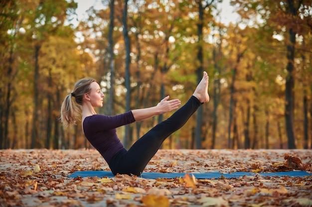 美しい若い女性は、秋の公園のウッドデッキでヨガのアーサナパリプルナナヴァサナポーズを練習します。
