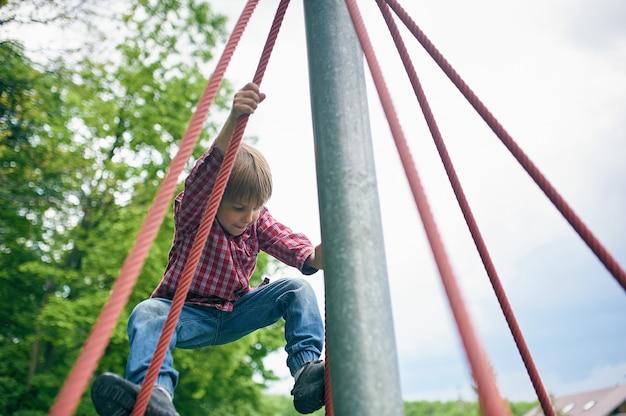 自然な緑の遊び場でかわいい幼児男の子の屋外ポートレート
