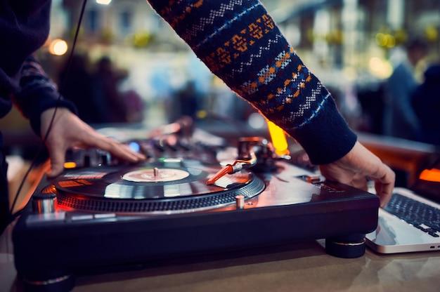 Поворотный стол, рука диджея на виниловой пластинке в ночном клубе.