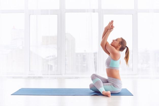 Красивая молодая женщина занимается йогой асаны гарудасана - поза орла в студии йоги