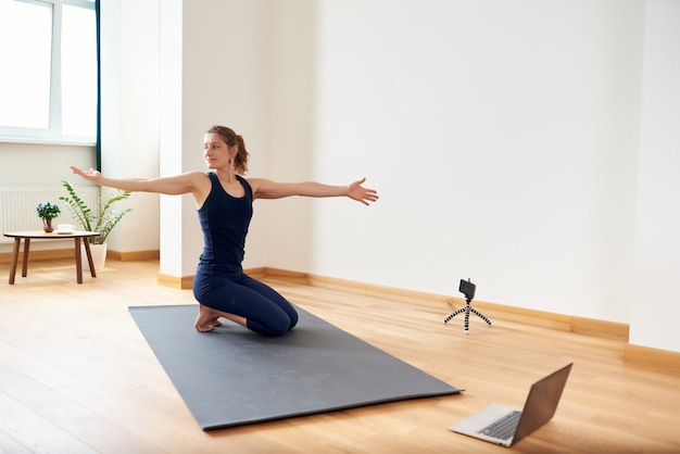 オンラインでヨガをしている女性。コンピューターと彼女のリビングルームのカメラ。健康的なライフスタイルと遠距離勤務のコンセプト