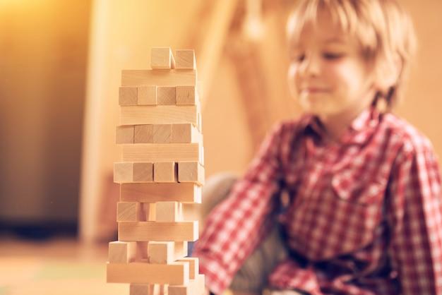 Дошкольный милый мальчик играет в настольную игру с деревянными блоками у себя дома