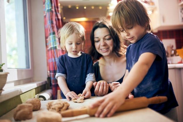 Счастливая семья веселые мальчики и их мама готовят тесто