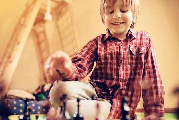 Милый дошкольник играет в шахматы дома