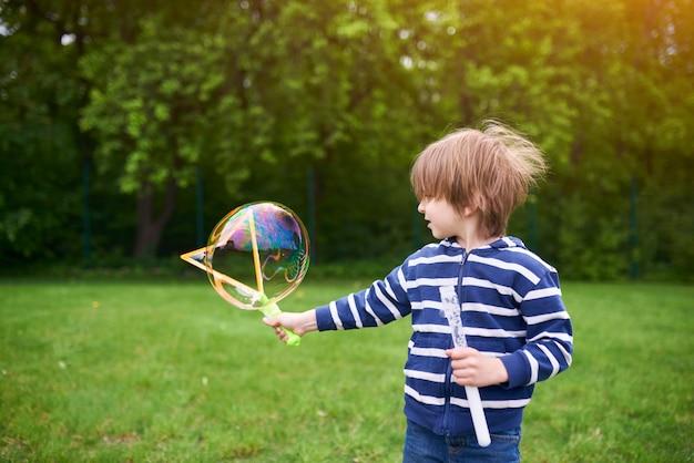 遊び場で緑の芝生でシャボン玉を吹くかわいい幼児男の子の屋外ポートレート。