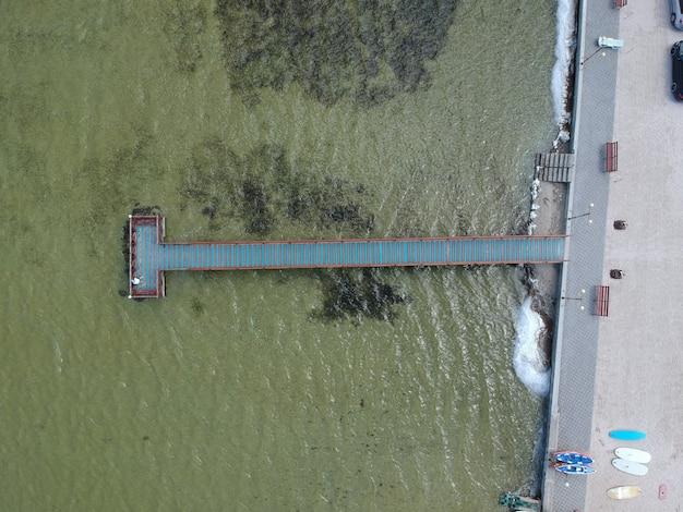 湖の上の木製の桟橋と青緑色の水の空撮