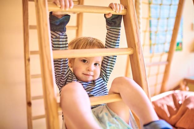 Двухлетний ребенок поднимается по лестнице на гимнастический комплекс дома
