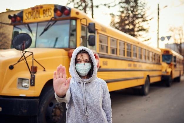 Женщина в защитной маске стоит перед школьным автобусом.