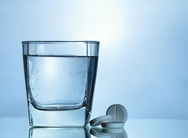 Шипучая таблетка возле стакана с водой