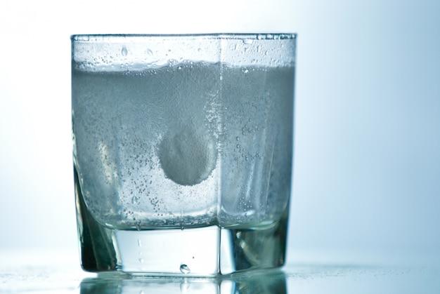 Шипучая таблетка в стакане с пузырьком