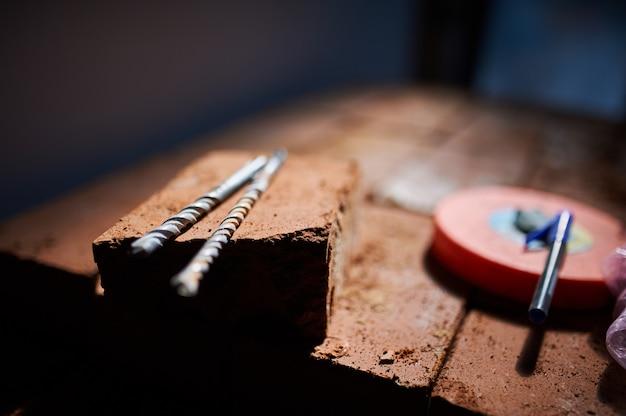 Строительный инструмент, дрели и кирпичи