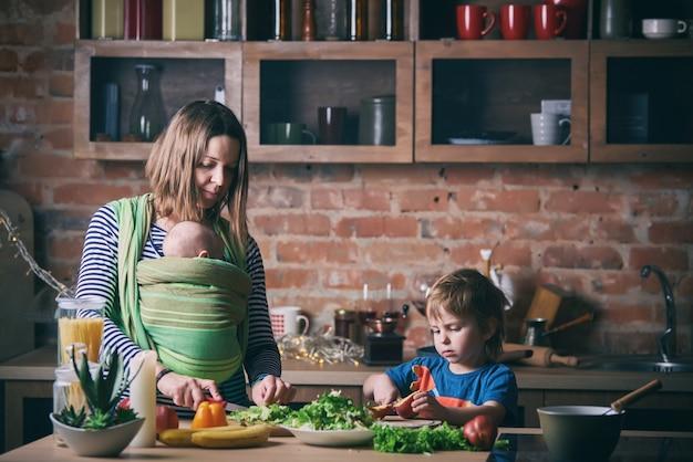 Счастливая молодая семья, красивая мать с двумя детьми, прелестный мальчик дошкольного возраста и ребенок в слинге, вместе готовить в солнечной кухне.
