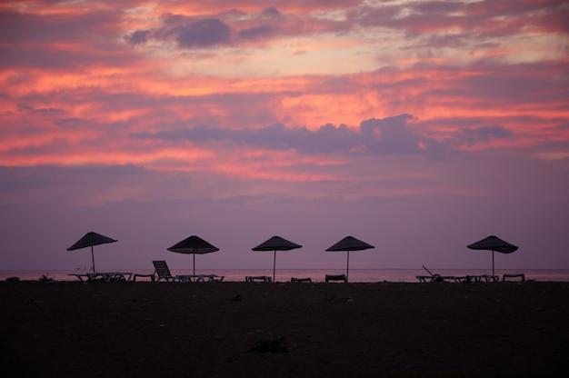 夕暮れ時のビーチパラソルのシルエット。海に沈む夕日。