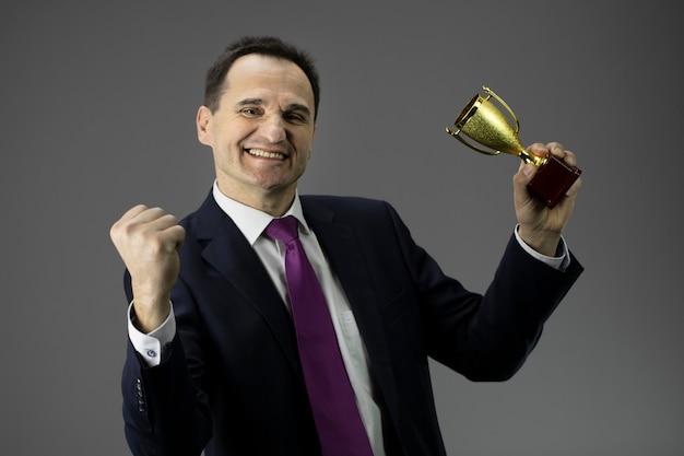優勝カップでジェスチャー幸せ満足しているビジネスマン。成功、目標の達成