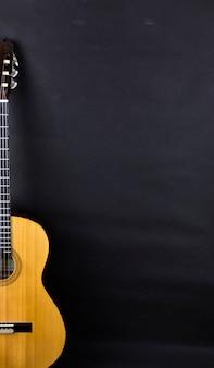 Половина оранжевой акустической гитары на черном фоне.