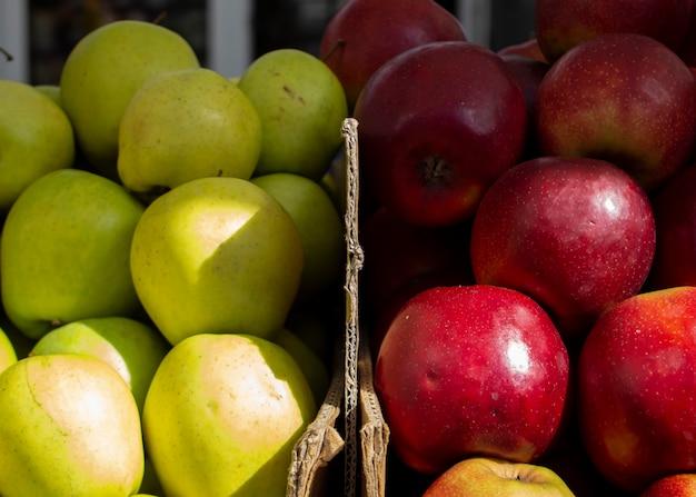 農家の市場でカラフルなフルーツカートンのジューシーな赤青リンゴ