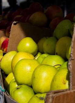 ファーマーズマーケットのカウンターのカートンでジューシーな緑赤いリンゴ
