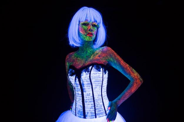 スタジオで暗い背景に紫外線の下で白いウェディングドレスで暗い少女に輝く流行の花嫁のネオン照明で結婚式のフォトセッションの概念