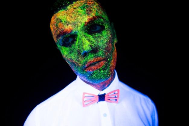 ヴォーグスタイルの新郎の若い男のネオン照明での結婚式のフォトセッションの概念は、スタジオで暗い背景に紫外線の下で蝶ネクタイと白いウェディングスーツで暗いポーズで輝く