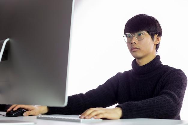 Красивый китайский человек в очках работает в офисе на компьютере.
