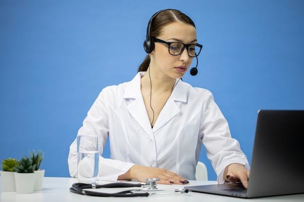 ビデオ通話で患者と話しているヘッドセットと白衣のセクシーな女医