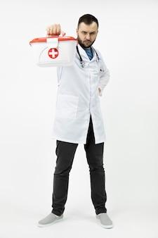 若いひげを生やした救急救命士持株赤十字医療キット