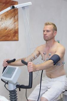 病院クリニックの男性患者に負荷テストで心電図を作成する心電図装置を持つ医師