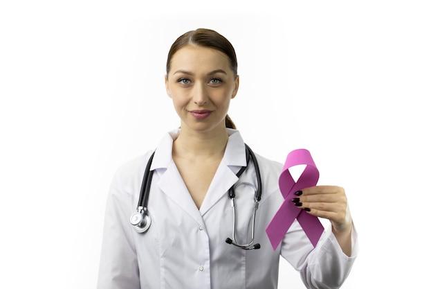 Улыбающаяся медсестра в белом халате и стетоскопе держит розовую ленту, символ октября