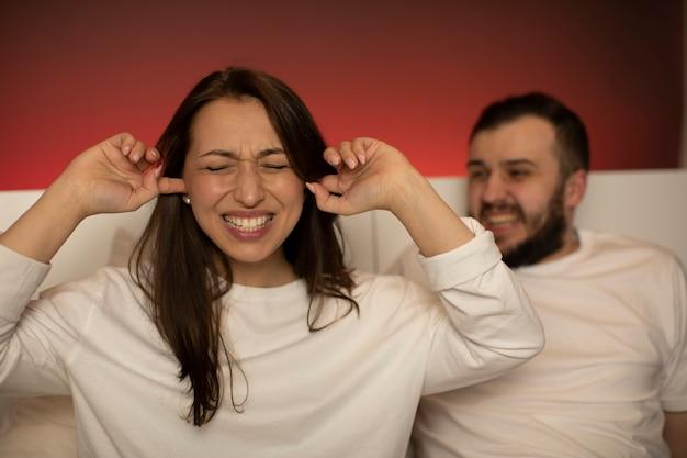 怒っている夫が喧嘩中に妻に叫ぶ泣いている女性の手で耳を閉じた