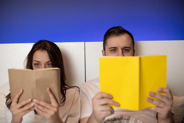 Красивая пара лежит в постели с бумажными книгами в руках, прячась за открытыми книгами