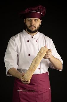 制服を着たハンサムなひげを生やしたシェフ男がバゲット、フランスパンの塊を保持しています。