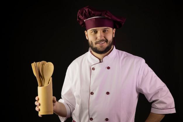 制服を着た笑顔のハンサムなシェフ男が木製キッチンツール用具を保持します