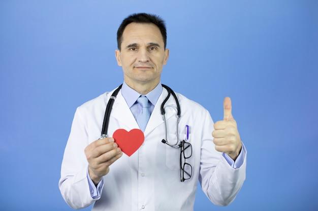 Врач со стетоскопом на ярко-синем держит сердце в руке и показывает как.
