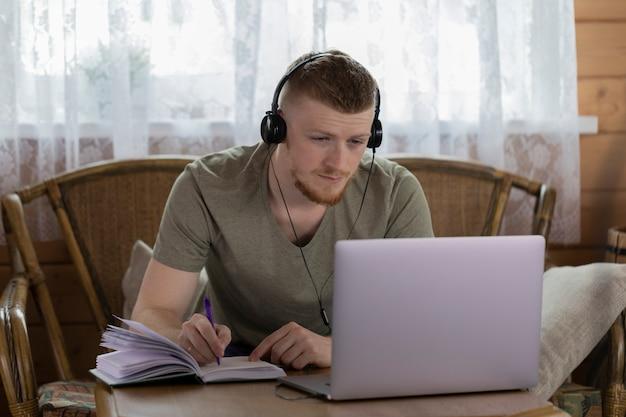 ヘッドフォンの若い男は木造住宅の日記にノートを作るラップトップで動作します