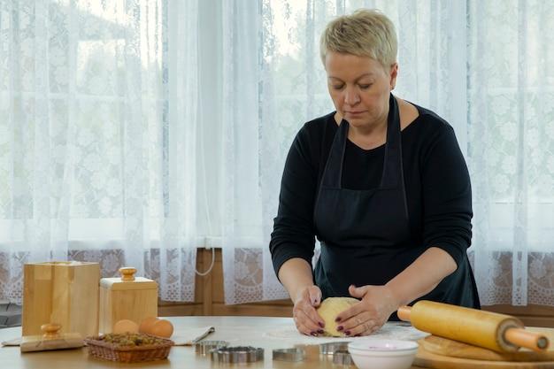 生地をマッシングする自家製クッキーを作る黒いエプロンの中年の女性