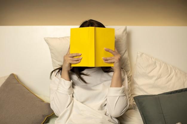 女性は彼女の顔をカバーする本を保持しています
