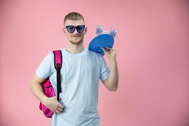 Портрет кавказского мальчика студента, держа скейтборд пенниборд на плече