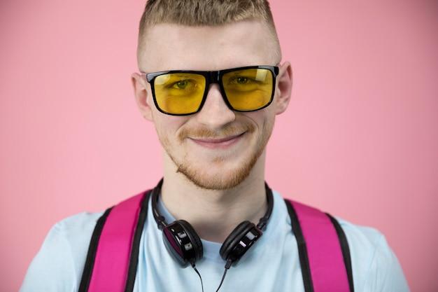 Портрет милого мальчика в желтых очках и наушниках на шее широко улыбается.