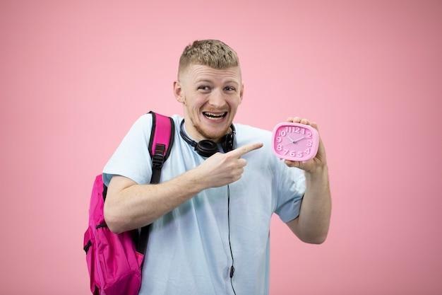 Возбужденный студент держит в руках будильник и указывает на набор. опоздал на встречу