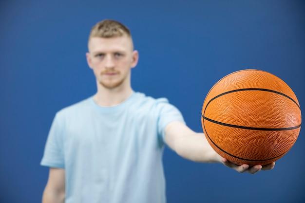 ひげを生やしたアメリカ人学生のバスケットボール選手は伸ばした腕にバスケットボールを保持しています。