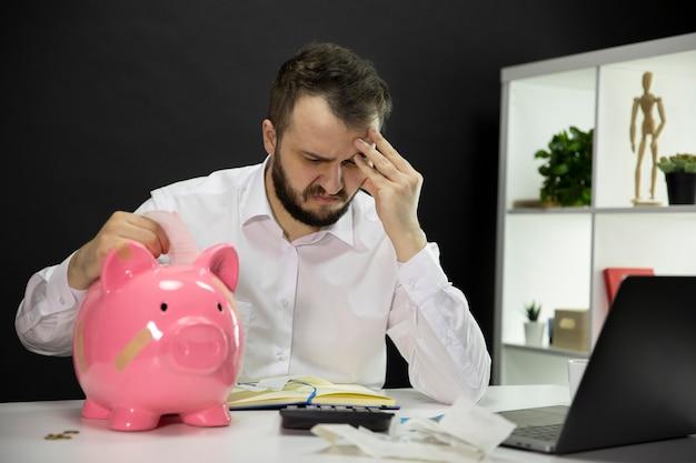 Бизнесмен в отчаянии, глядя на счета с сломанной копилку на переднем плане