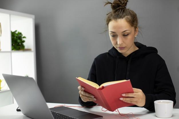 自己分離中にホームオフィスで本を読んで若い美しい女性