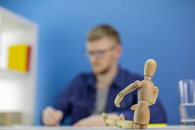 Сосредоточиться на манекене. художник работает над эскизами, рисует карандашом человеческую фигуру
