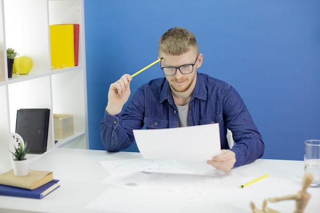 Концентрированный дизайнер, глядя на карандашные эскизы макет, держа карандаш в храме